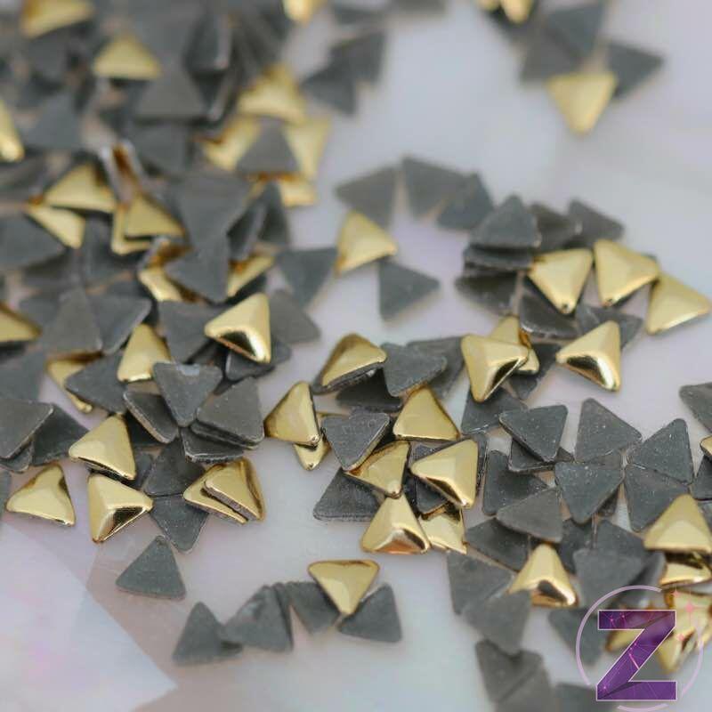 szegecs körömdísz háromszög formában arany színben